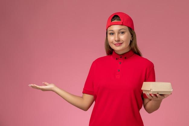 Correio feminino de frente para o uniforme vermelho e capa segurando um pacote de comida de entrega no fundo rosa.