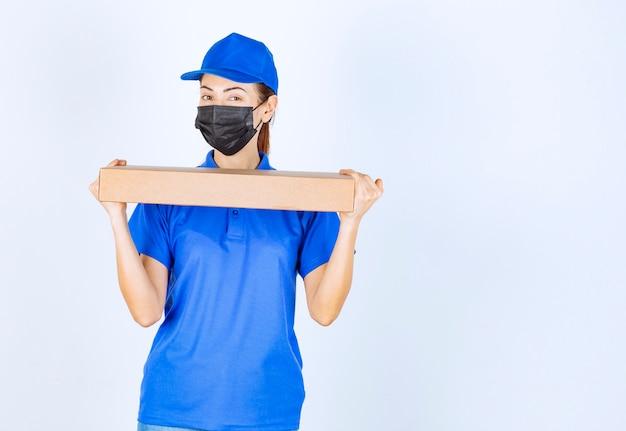 Correio feminino de uniforme azul e máscara facial entregando uma caixa de papelão ao cliente.