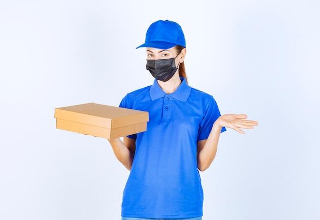 Correio feminino de uniforme azul e máscara facial, segurando uma caixa de papelão e apontando para algum lugar.
