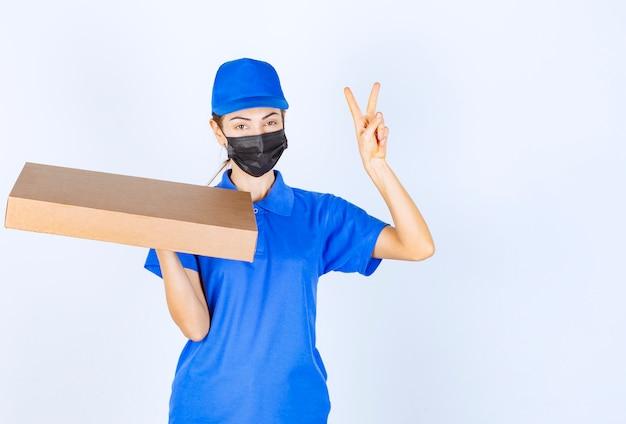 Correio feminino de uniforme azul e máscara facial, segurando uma caixa de papelão e mostrando sinal de mão de prazer.