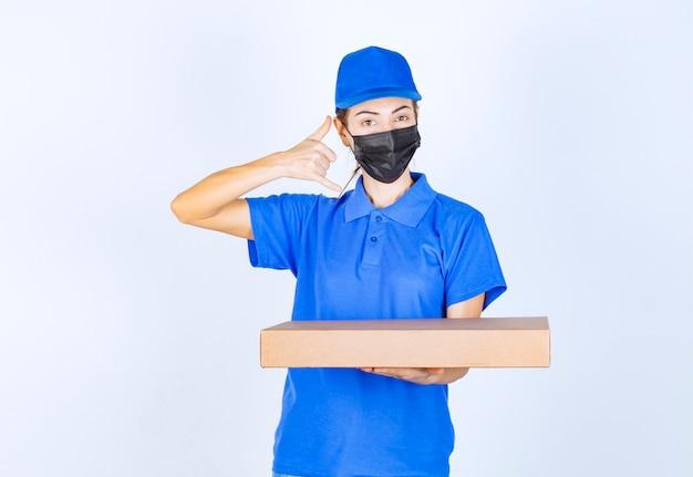Correio feminino de uniforme azul e máscara facial, segurando uma caixa de papelão e pedindo uma ligação.