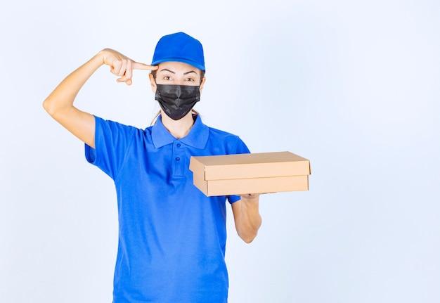 Correio feminino de uniforme azul e máscara facial, segurando uma caixa de papelão e pensando na entrega.