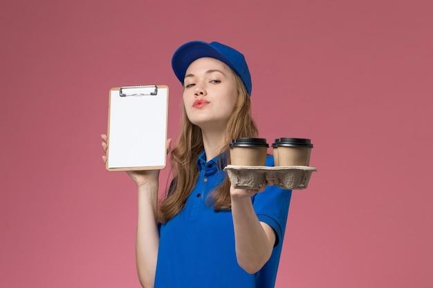 Correio feminino de uniforme azul segurando um bloco de notas e entregando xícaras de café na mesa de trabalho rosa-luz