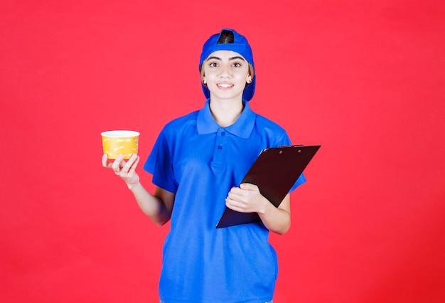 Correio feminino de uniforme azul, segurando um copo de macarrão amarelo e uma pasta preta.