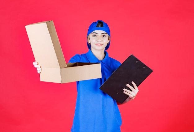 Correio feminino de uniforme azul segurando uma pasta preta e dando a caixa de papelão para viagem ao cliente.
