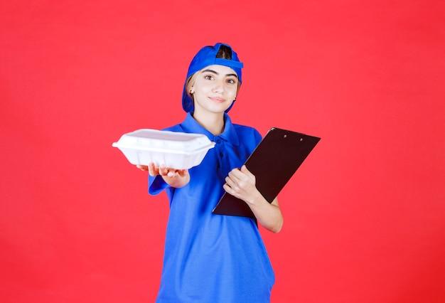 Correio feminino de uniforme azul, segurando uma pasta preta e dando uma caixa branca para viagem para o cliente.
