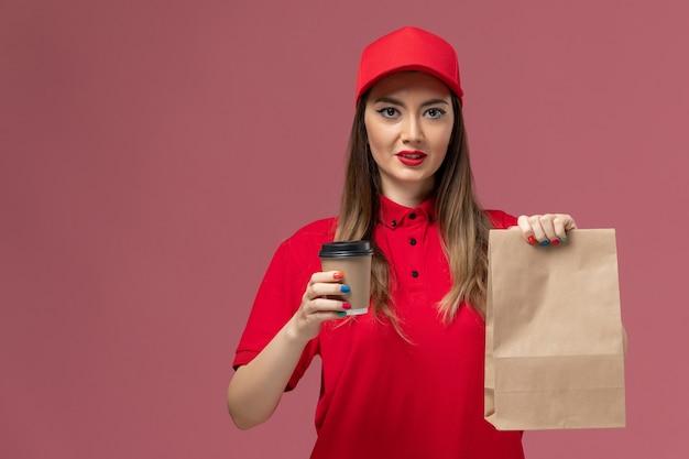 Correio feminino de uniforme vermelho segurando uma xícara de café de entrega e um pacote de comida na mesa rosa trabalho de entrega de serviço