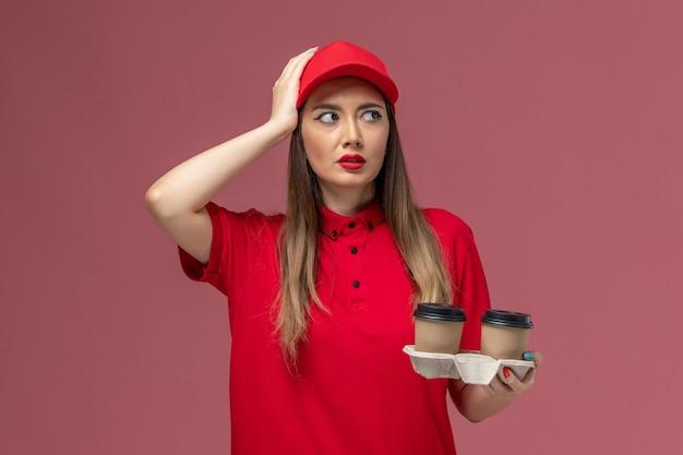 Correio feminino de uniforme vermelho segurando xícaras de café marrom e pensando no fundo rosa claro uniforme de entrega de serviço