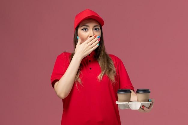Correio feminino de uniforme vermelho segurando xícaras de café marrom em fundo rosa claro serviço de entrega uniforme de trabalho feminino empresa de vista frontal