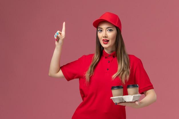 Correio feminino de uniforme vermelho segurando xícaras de café marrom em fundo rosa claro.