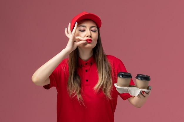 Correio feminino de uniforme vermelho segurando xícaras de café marrons em fundo rosa claro.