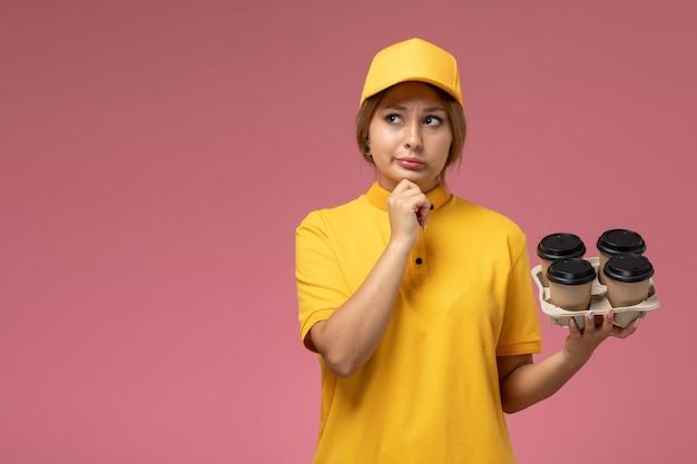 Correio feminino de vista frontal com capa amarela uniforme amarela segurando copos de café de plástico pensando no fundo rosa uniforme entrega trabalho cor trabalho