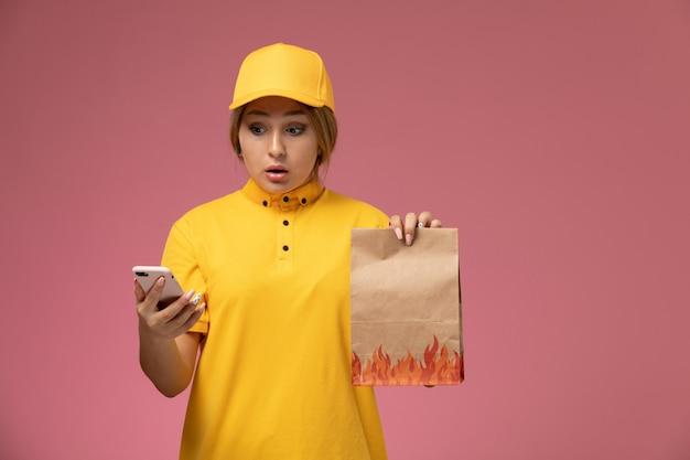 Correio feminino de vista frontal com capa amarela uniforme amarela segurando pacote de comida e usando smartphone em trabalho de cor de entrega uniforme de fundo rosa