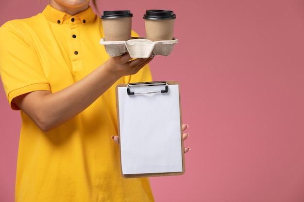 Correio feminino de vista frontal com capa amarela uniforme segurando café e bloco de notas sobre o trabalho de entrega uniforme de fundo rosa