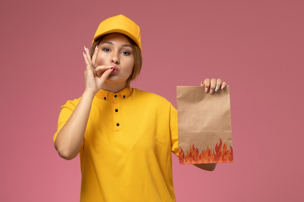 Correio feminino de vista frontal com capa amarela uniforme segurando o pacote de entrega no trabalho de entrega uniforme de fundo rosa
