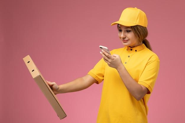 Correio feminino de vista frontal com capa amarela uniforme segurando um pacote de comida usando o telefone no trabalho de entrega uniforme de fundo rosa