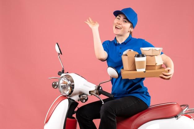 Correio feminino de vista frontal com pacotes de comida e caixas na cor rosa serviço de entrega de comida de bicicleta uniforme