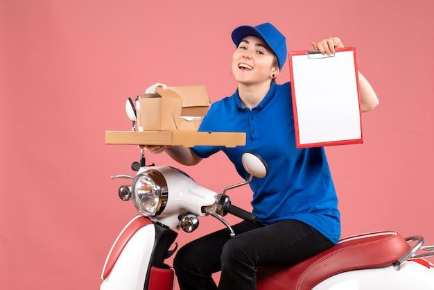 Correio feminino de vista frontal com pacotes de comida e nota de arquivo no serviço de uniforme de bicicleta de entrega de comida de trabalhador cor-de-rosa