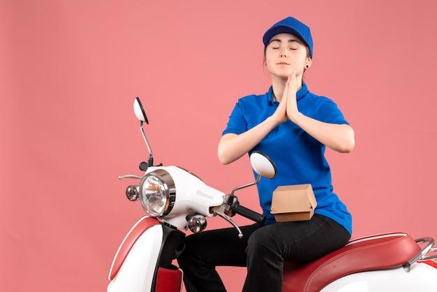 Correio feminino de vista frontal com pequeno pacote de comida na bicicleta de entrega de comida uniforme cor rosa