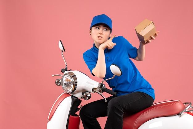 Correio feminino de vista frontal com pequeno pacote de comida no uniforme rosa do trabalho.