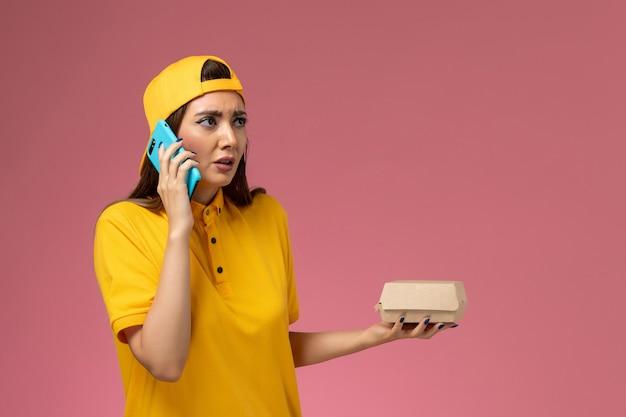 Correio feminino de vista frontal com uniforme amarelo e capa segurando um pacote de comida e falando ao telefone na parede rosa claro.