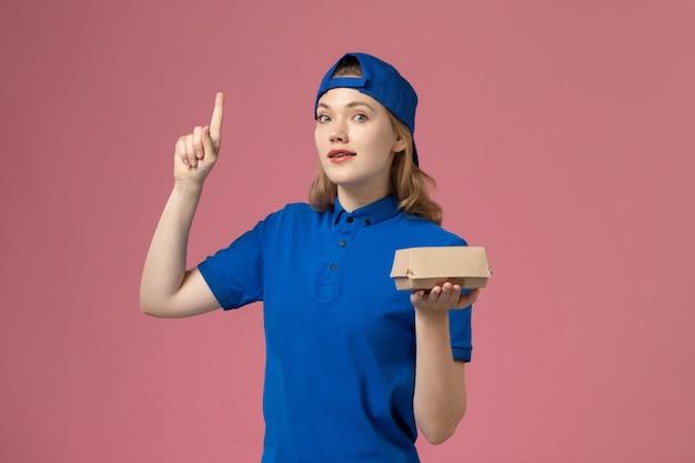 Correio feminino de vista frontal com uniforme azul e capa segurando um pequeno pacote de entrega de comida no fundo rosa.