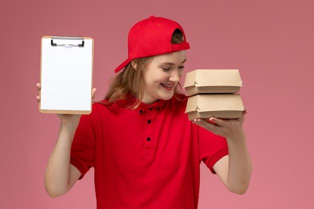 Correio feminino de vista frontal com uniforme vermelho e capa segurando o bloco de notas e pequenos pacotes de comida para entrega rindo sobre fundo rosa claro.