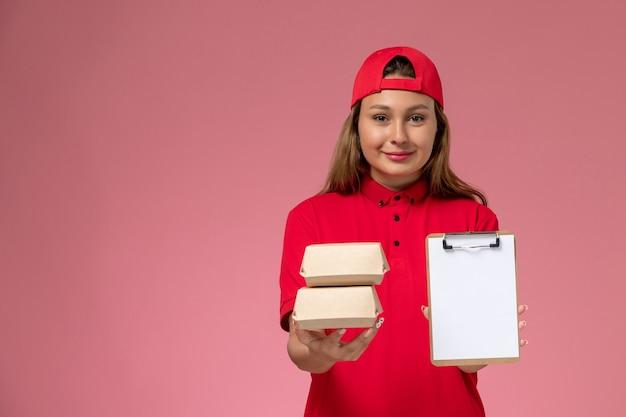 Correio feminino de vista frontal com uniforme vermelho e capa segurando o bloco de notas e pequenos pacotes de entrega de comida no fundo rosa. serviço de entrega de uniforme de trabalho