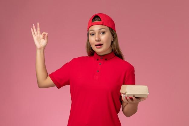 Correio feminino de vista frontal com uniforme vermelho e capa segurando pacote de comida de entrega no serviço de entrega uniforme de fundo rosa