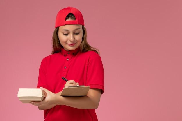 Correio feminino de vista frontal com uniforme vermelho e capa segurando um pequeno pacote de comida de entrega e um bloco de notas escrito na parede rosa, serviço de entrega de uniforme de trabalho