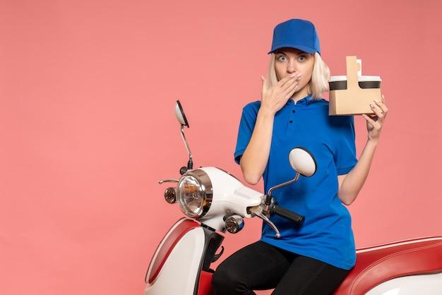 Correio feminino de vista frontal com xícaras de café no trabalho de entrega rosa trabalho de uniforme trabalhador