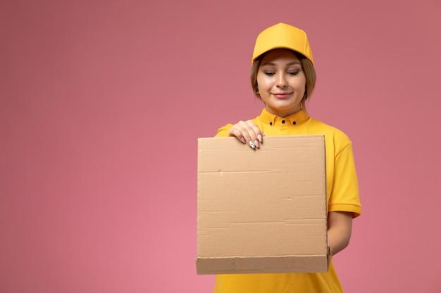 Correio feminino de vista frontal em uniforme amarelo capa amarela segurando e abrindo a caixa de comida na mesa rosa uniforme entrega cor feminina