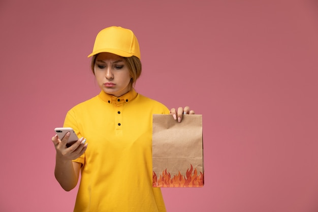 Correio feminino de vista frontal em uniforme amarelo capa amarela segurando um pacote de comida usando um telefone no fundo rosa uniforme entrega trabalho cor trabalho