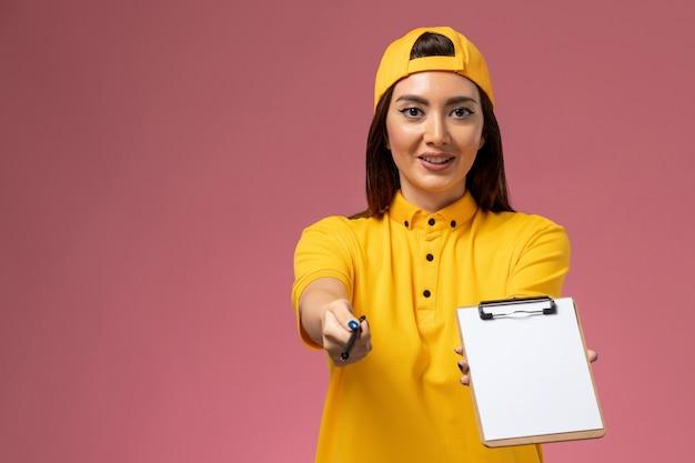 Correio feminino de vista frontal em uniforme amarelo e capa segurando o bloco de notas e uma caneta na parede rosa claro.