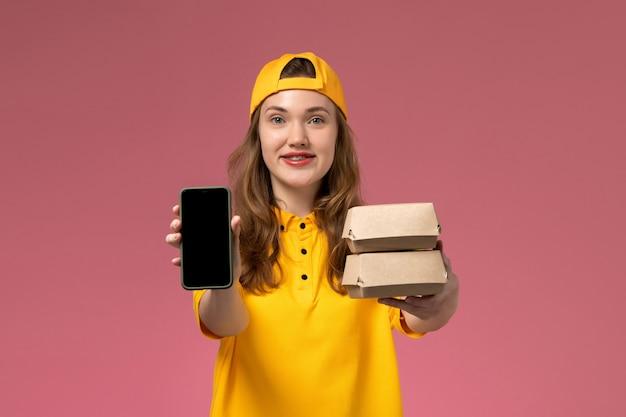 Correio feminino de vista frontal em uniforme amarelo e capa segurando o telefone com pacotes de comida na parede rosa empresa serviço de entrega de uniforme trabalho