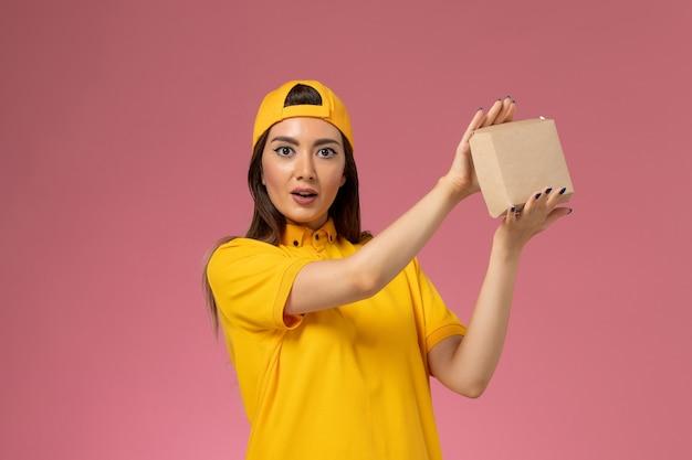 Correio feminino de vista frontal em uniforme amarelo e capa segurando um pequeno pacote de entrega de comida na empresa de entrega de uniforme de serviço de parede rosa claro