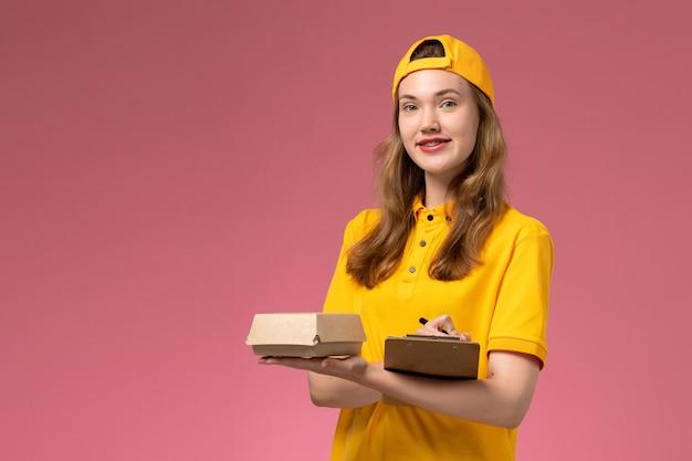 Correio feminino de vista frontal em uniforme amarelo e capa segurando uma caneta de pacote de comida para entrega e um bloco de notas na parede rosa claro.