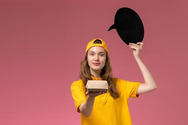 Correio feminino de vista frontal em uniforme amarelo e capa segurando uma placa preta com tigela na parede rosa serviço de entrega uniforme da empresa trabalho