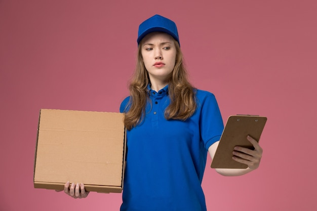 Correio feminino de vista frontal em uniforme azul segurando a caixa de entrega de comida e o bloco de notas com expressão confusa na empresa de emprego de uniforme de serviço de mesa rosa