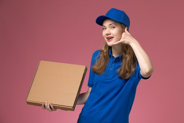 Correio feminino de vista frontal em uniforme azul segurando uma caixa de comida e sorrindo no fundo rosa.