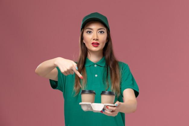 Correio feminino de vista frontal em uniforme verde e capa segurando copos de café de entrega na parede rosa empresa serviço trabalho uniforme entrega feminino