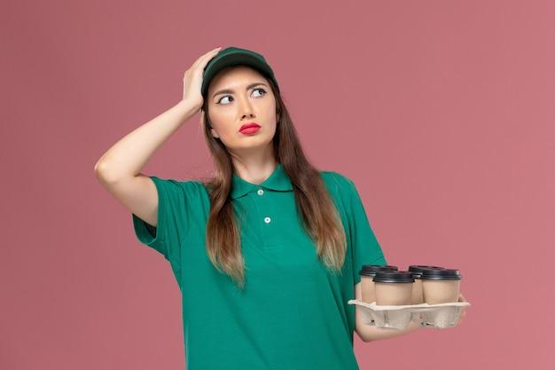 Correio feminino de vista frontal em uniforme verde e capa segurando copos de café de entrega pensando na parede rosa serviço uniforme trabalho de entrega