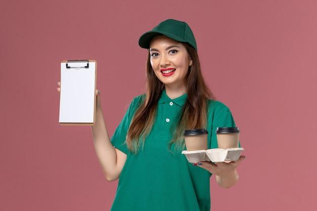 Correio feminino de vista frontal em uniforme verde e capa segurando xícaras de café de entrega e bloco de notas na parede rosa.