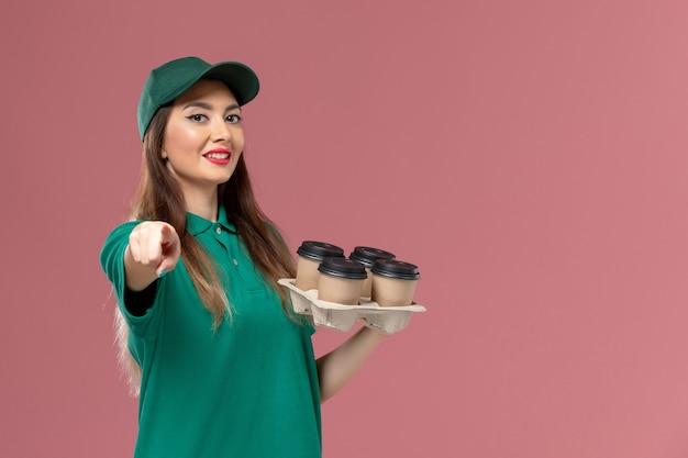 Correio feminino de vista frontal em uniforme verde e capa segurando xícaras de café sorrindo na parede rosa serviço uniforme trabalho de entrega