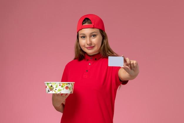 Correio feminino de vista frontal em uniforme vermelho e capa segurando a tigela de entrega e o cartão na parede rosa, trabalhador de trabalho de serviço de entrega de uniforme