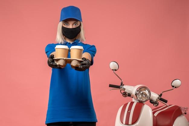 Correio feminino de vista frontal segurando xícaras de café na rosa