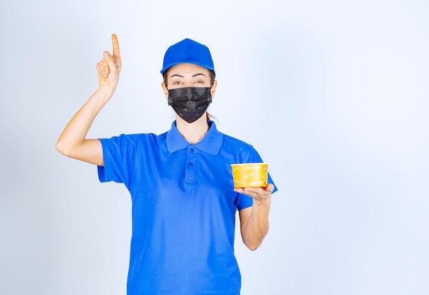 Correio feminino do restaurante de uniforme azul e máscara facial, segurando uma comida para viagem e apontando para algum lugar.