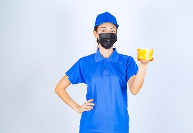 Correio feminino do restaurante de uniforme azul e máscara facial, segurando uma comida para viagem.