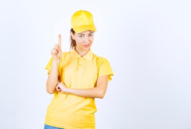 Correio feminino em uniforme amarelo, apontando para algum lugar.