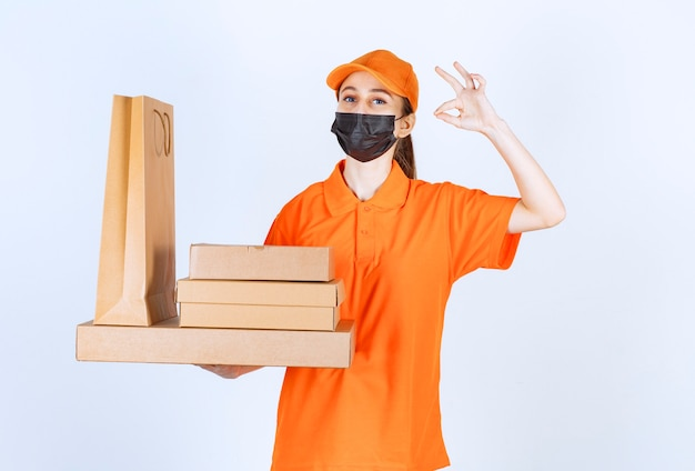 Correio feminino em uniforme amarelo e máscara preta segurando vários pacotes de papelão e sacola de compras e mostrando sinal de mão positivo.